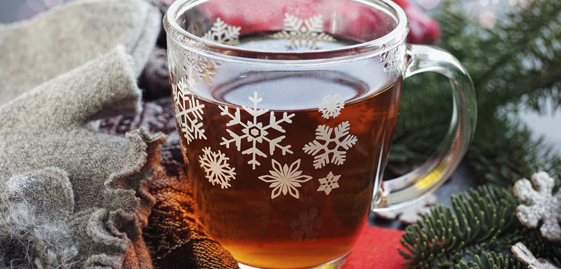 glass mug with a snowflake pattern and an amber liquid inside