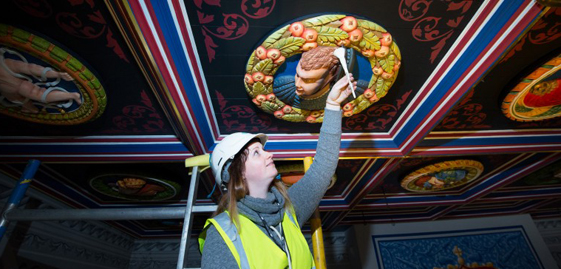 woman in hard hat and hi vis vest reaches up to dust wooden ceiling