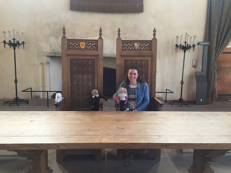 Megan Murray with three kitted characters, sitting in a throne at the head table of the Great Hall at Stirling Castle.