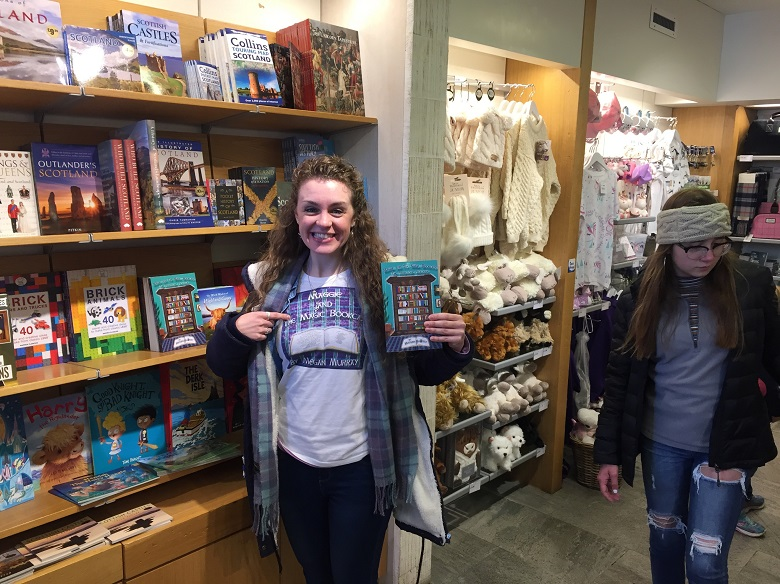 Megan Murray posing with a copy of her book in the Stirling Castle Bookshop