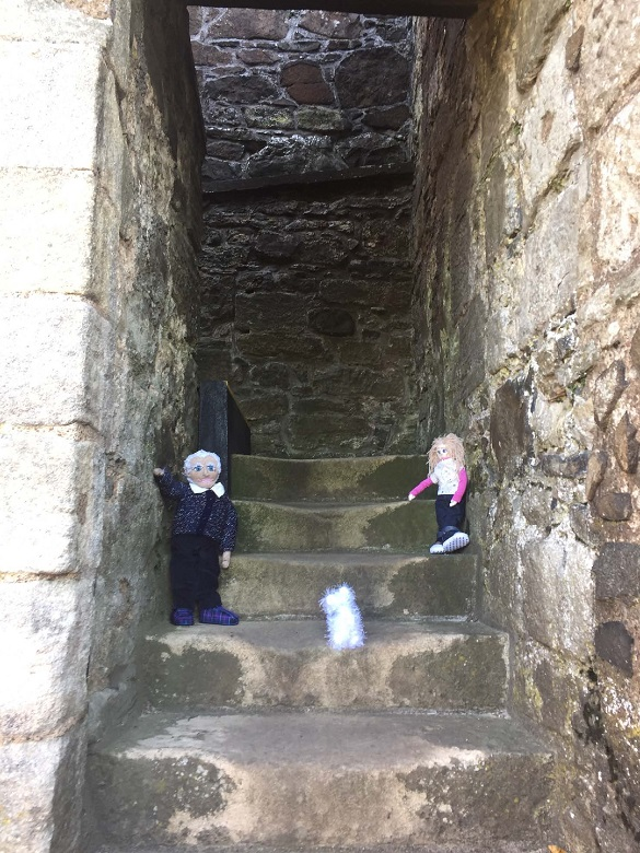 Worn stone steps with knitted versions of Maggie, grandpa and Wally placed on them