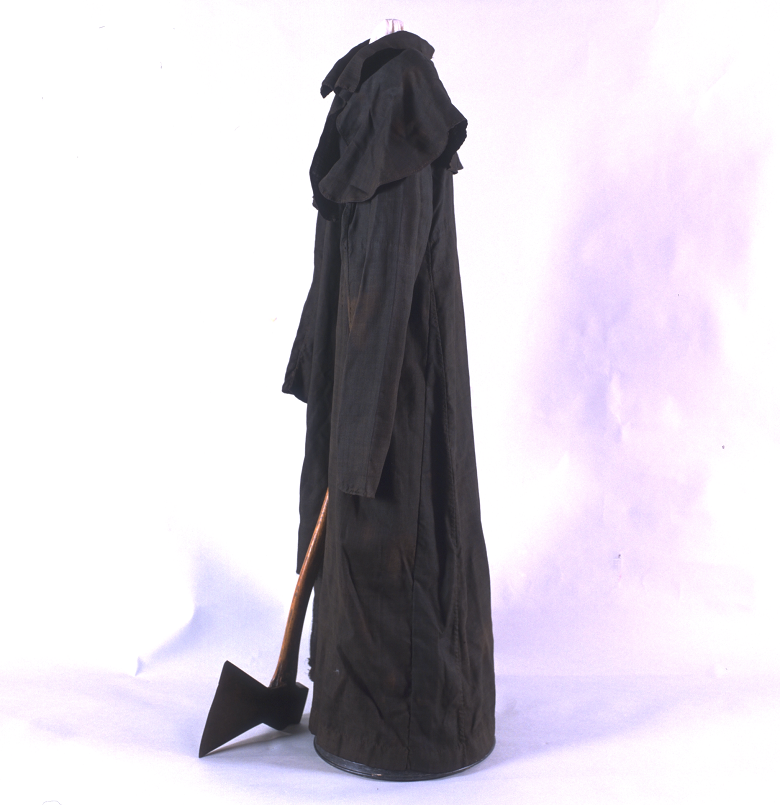 A black headsman outfit on display with an axe