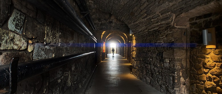 A visitor walking through a corridor in the Stirling Castle vaults