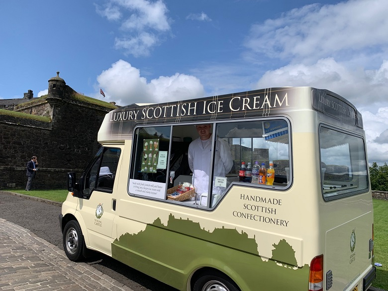 An ice cream seller poses in his van, parked in front of Stirling Castle. It is decorated with the castle logo and and an outline of the castle.