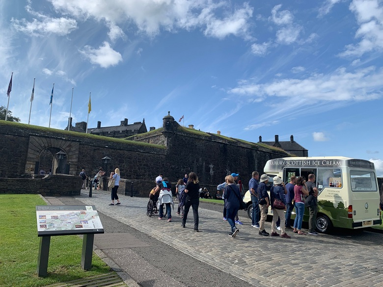 Visitors queue at an ice cream van in front of Stirling Castle