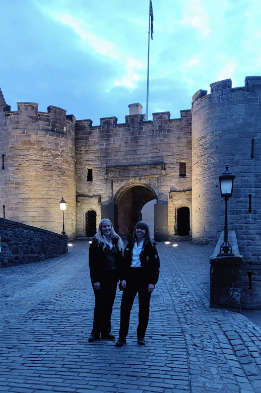 Stirling Castle staff members pose in front of the castle gates at an evening event