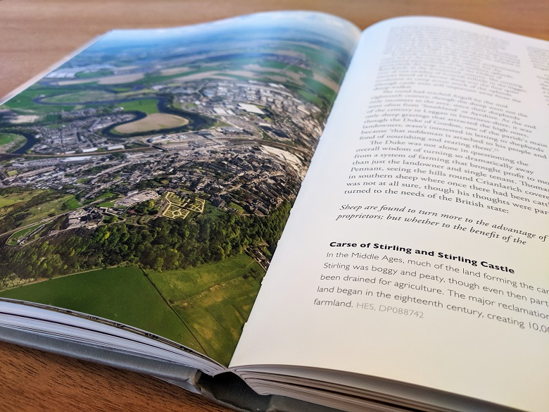 An open copy of a large coffee table book with a colourful aerial photo on one page