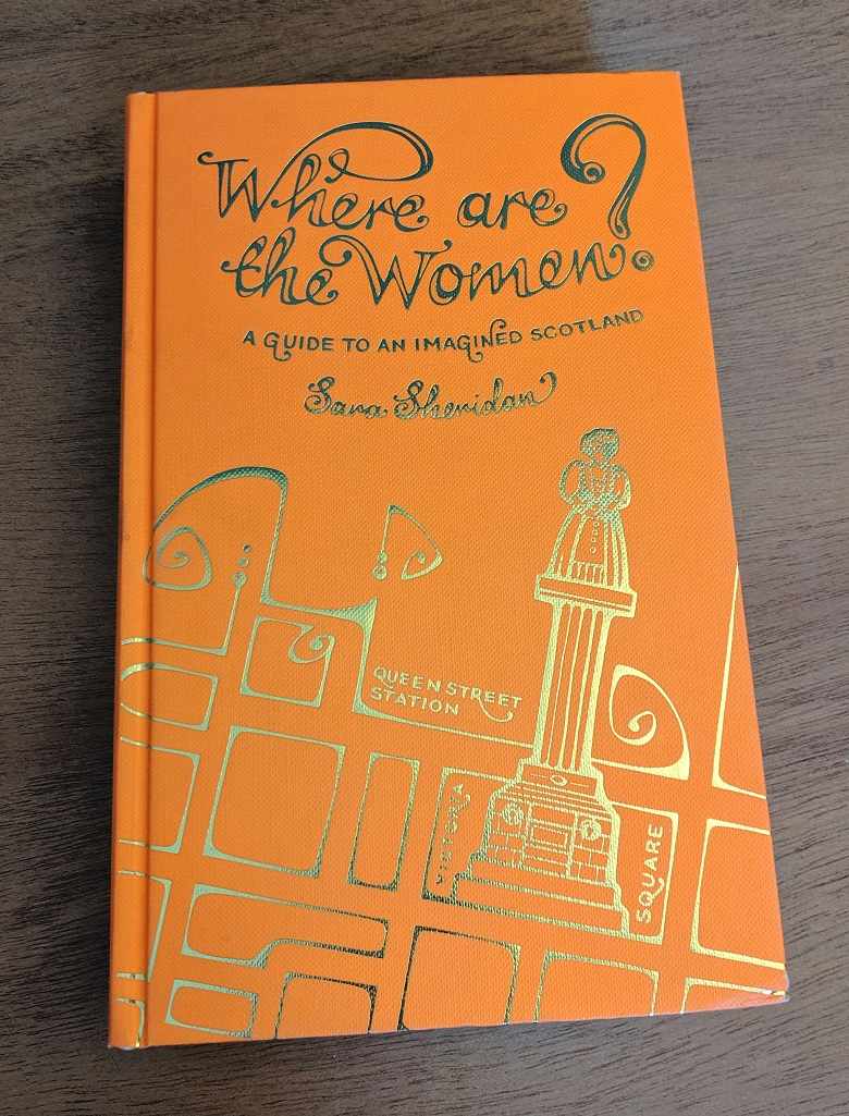 Hardcover copy of Where Are The Women. The title and cover image are in gold against a bright orange background