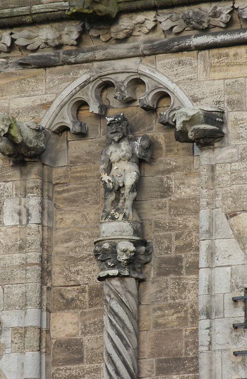 A stone carving of the devil on the side of a castle building
