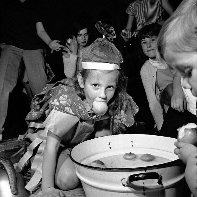Archive photo of a young girl dooking for apples at a Halloween party
