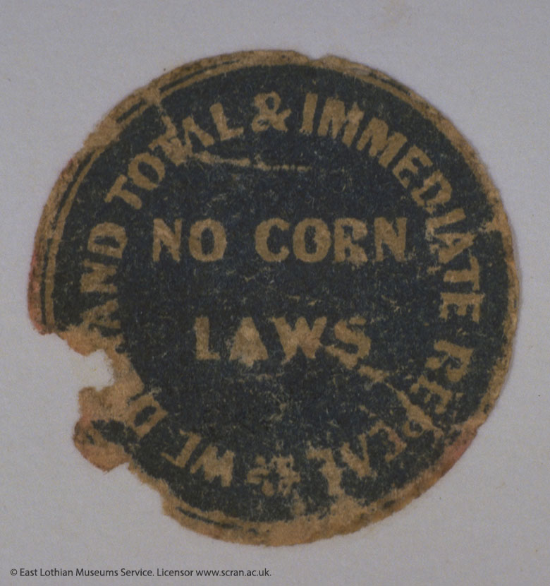 "A round sticker. The middle says ""No corn laws"". Around the outside it reads: ""WE DEMAND TOTAL AND IMMEDIATE REPEAL"""