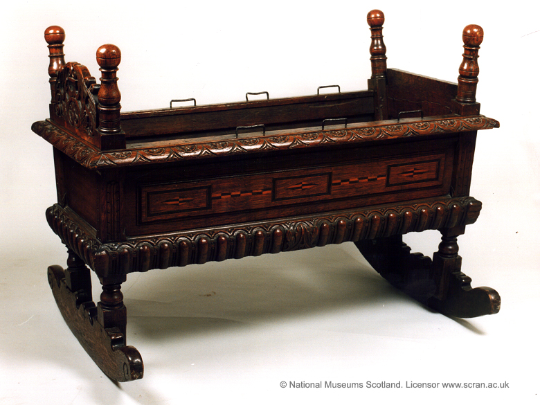 A dark wooden cradle with ornate decorations on rockers.
