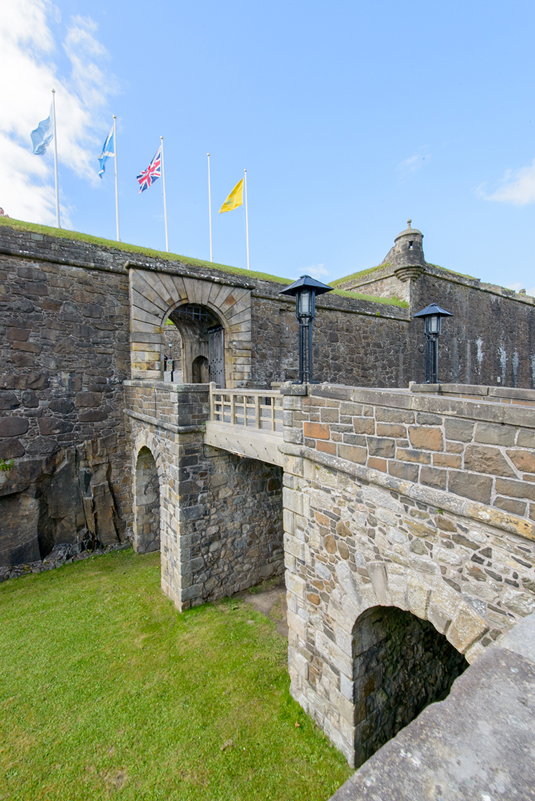 the Outer Defences at Stirling Castle. Three flags fly above the entrance archway.