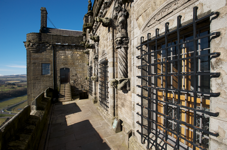 An open walkway leads to some steps and a door. On the left is a view over the landscape. On the right is a castle wall with barred windows and carved decoration.