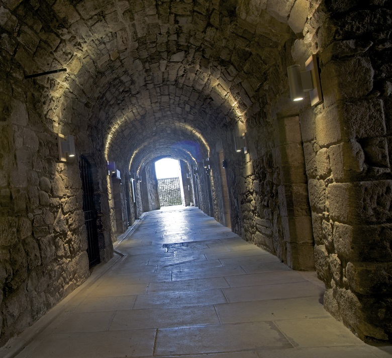 A long, vaulted tunnel with doors leading off it. THere is daylight coming from the end of the tunnel
