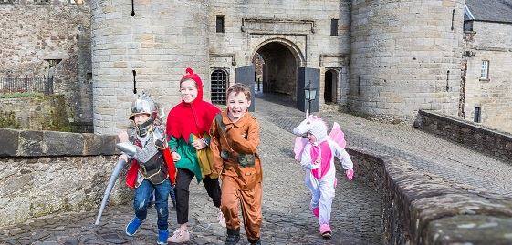 Children in historic fancy dress running out of the gates of Stirling Castle