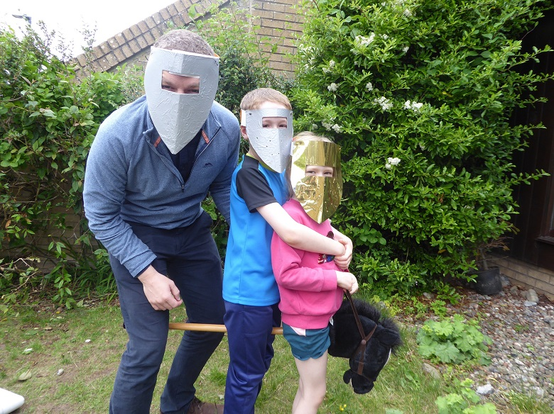 An adult and two children wearing homemade jousting helmets
