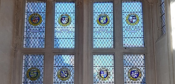 A stained glass window with 8 heraldic crests