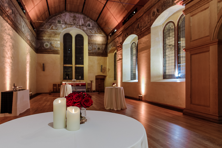 Tables decorated with candles in a historic chapel building