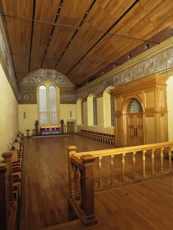 The lavishly decorated interior of a royal chapel with wooden panelling on the walls and a curved wooden ceiling
