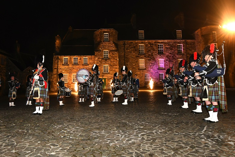 A pipe band dressed in kilts performing in an illuminated castle courtyard