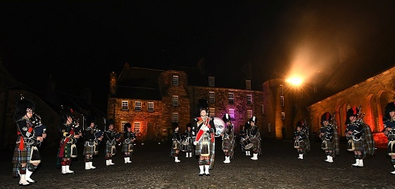 A pipe band performing in a castle courtyard at night