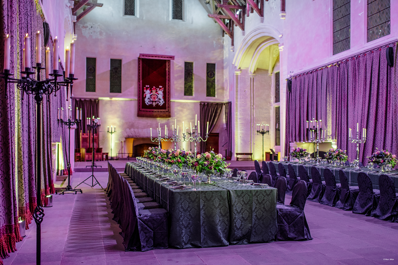 Two large banqueting tables laid out for an event in the great hall of a castle