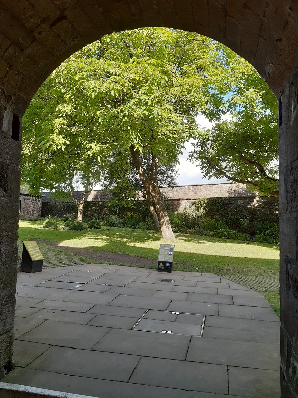An archway leading into a castle garden