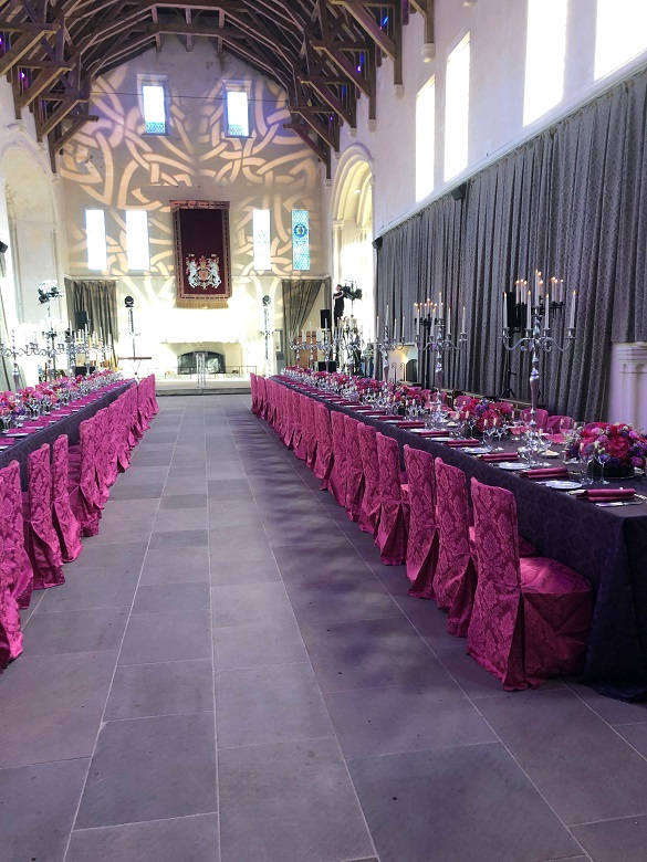 Two long dining tables decorated with red tablecloths, candlesticks and flowers running the width of the great hall in a castle. A glimpse of an impressive timbered roof is above.
