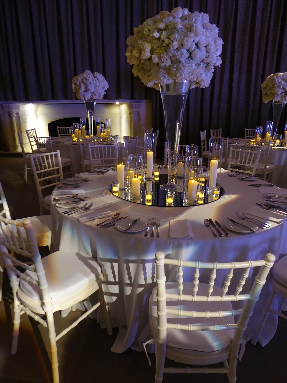 A large display of white flowers surrounded by candles in the centre of a circular table