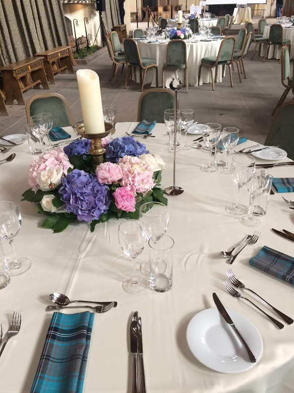 A large candle in the centre of a set dining table surrounded by pink, purple and white flowers