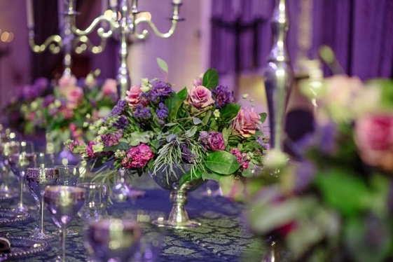 A silver vase filled with pink and blue flowers on a lavishly decorated banqueting table