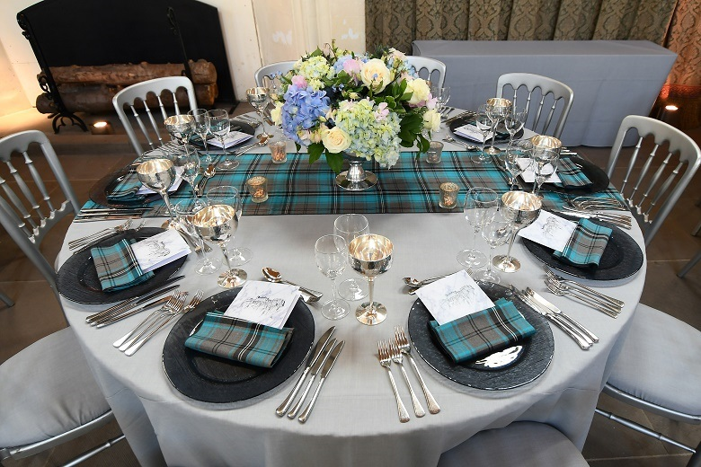 A circular dining table decorated with a tartan tablecloth and a vase of colourful flowers