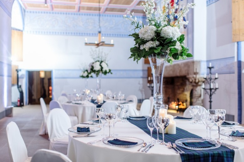 Elegant dining tables beside a large stone fireplace in a finely decorated room within a castle.
