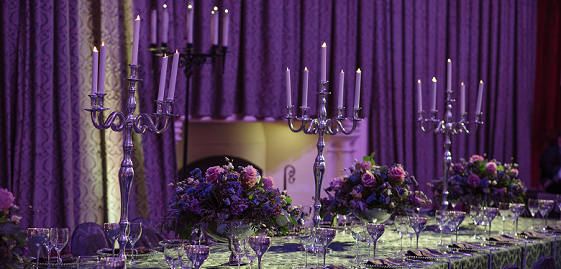 Candles, glasses and flowers on a long dining table