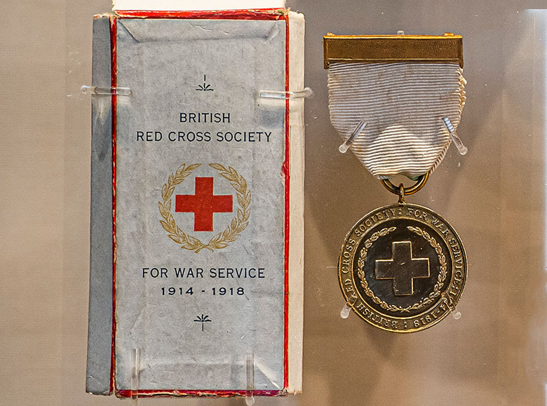 A Victoria Cross medal in a display cabinet, alongside its presentation box
