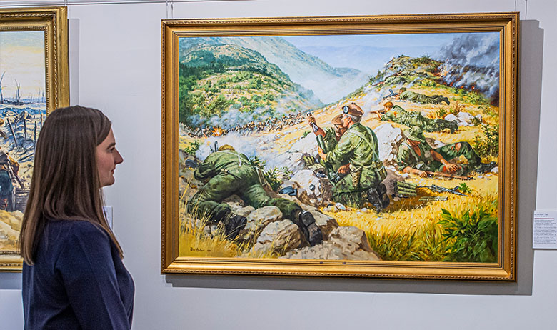 a woman looks at a painting depicting soldiers in mid-20th century uniform engaged in battle rural landscape