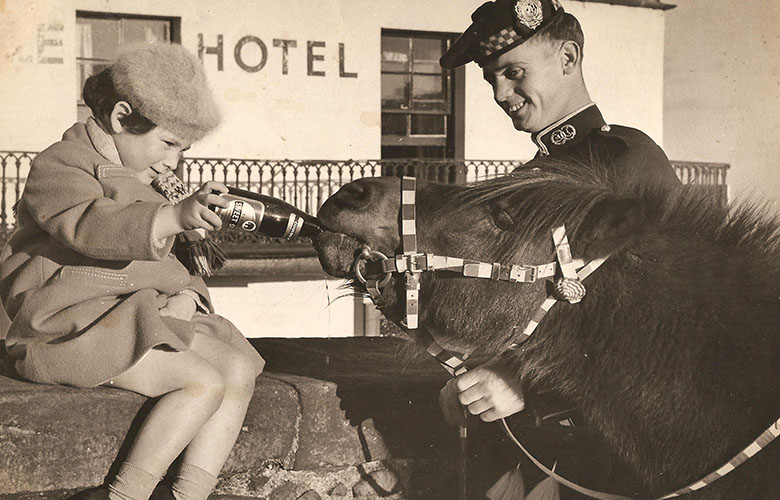 photo taken in the mid-20th century of a child feeding a bottle of beer to a small pony