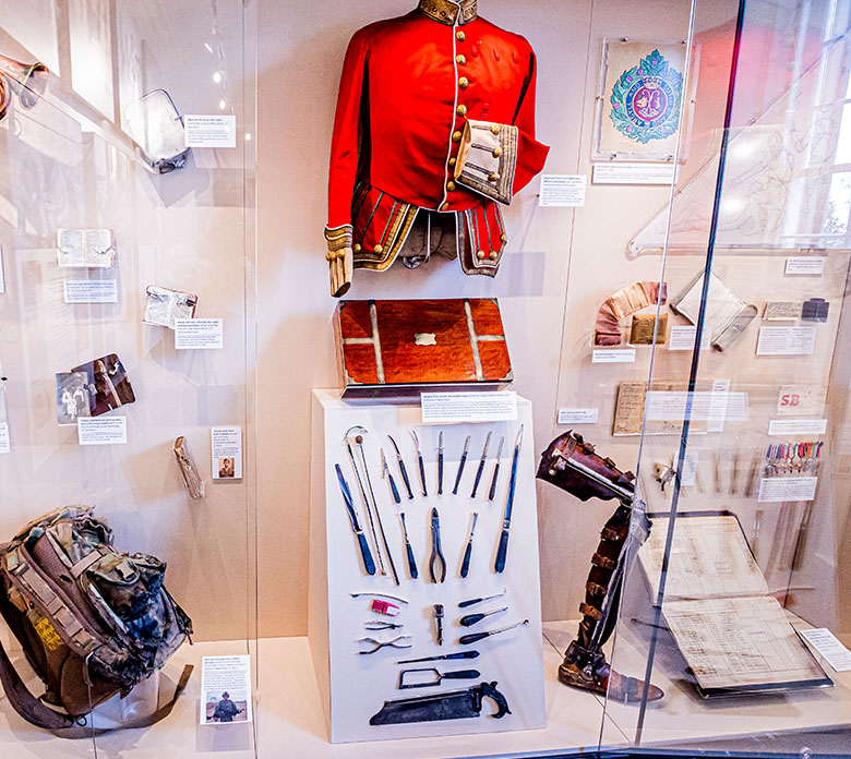 a museum display, featuring a red military coat, surgical instruments and a prosthetic leg